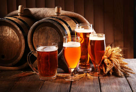 mug of ale: Beer barrel with beer glasses on table on wooden background