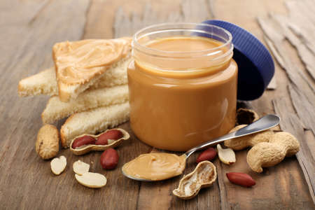 Creamy peanut butter in jar, on wooden table photo