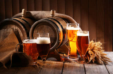 beer background: Beer barrel with beer glasses on table on wooden background