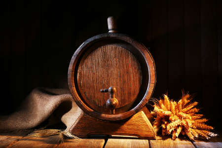 Old barrel with wheat on table on wooden background photo