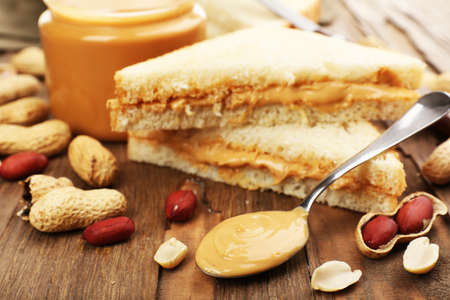 Bread slices with creamy peanut butter on wooden table photo