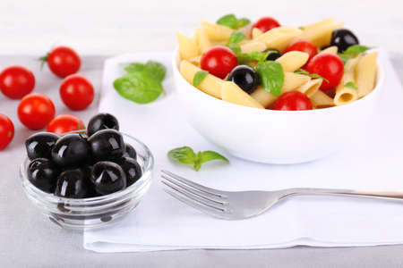 Pasta with tomatoes, olives and basil leaves in bowl on napkin on fabric background photo