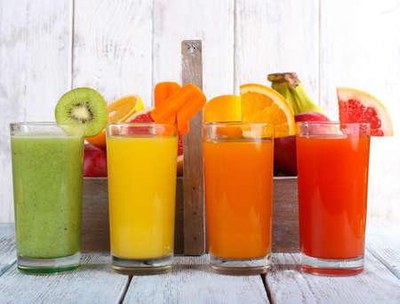 jugos: Frutas y jugo de verduras en vidrios y frutas frescas en la caja en la mesa de madera sobre fondo de pared de madera Foto de archivo
