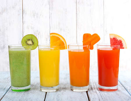 shot: Fruit and vegetable juice in glasses and pieces of fresh fruits on wooden table on wooden wall background