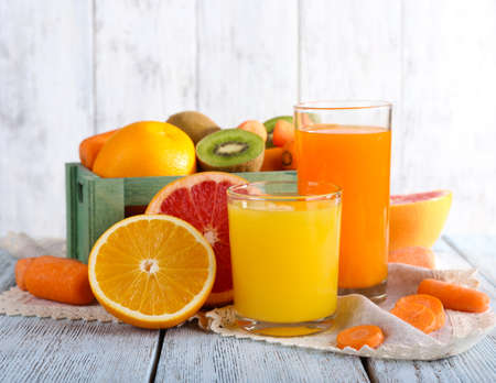 Fruit and vegetable juice in glasses and fresh fruits in box on wooden table on wooden wall background Stock Photo