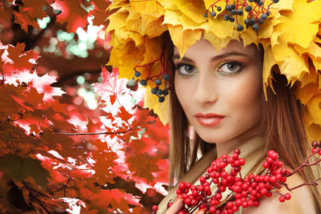 Beautiful young woman with yellow autumn wreath outdoors photo