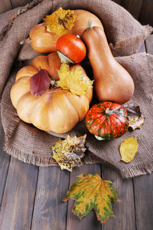 Pumpkins on sackcloth on wooden background photo