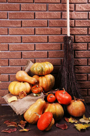 Pumpkins on stool on floor on brick wall background photo
