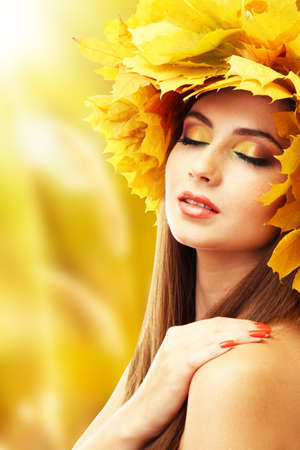 Beautiful young woman with yellow autumn wreath photo