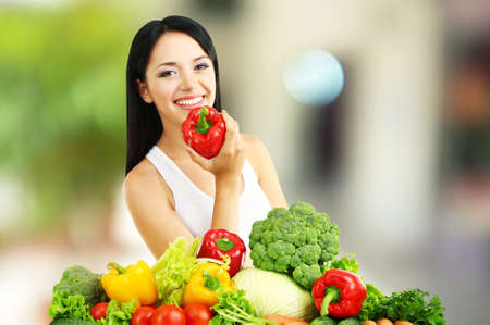 Girl with vegetables on shop background photo