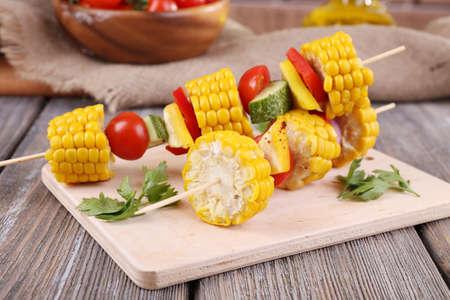 Sliced vegetables on picks on board on table close-up photo