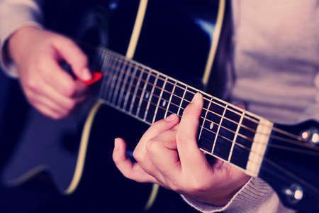 Acoustic guitar in female hands, close-up photo