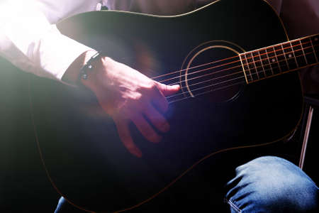hand jamming: Young musician playing acoustic guitar, on dark background