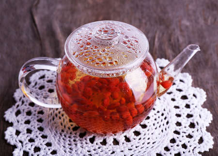 wolfberry: Goji berries drink in glass teapot on lace napkin on wooden background Stock Photo