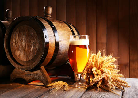 Beer barrel with beer glass on table on wooden  photo