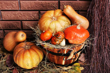 Pumpkins in wooden tub on floor on brick wall  photo
