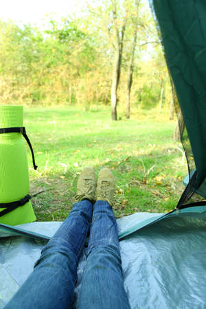 karemat: Legs lying in tourist tent in a forest