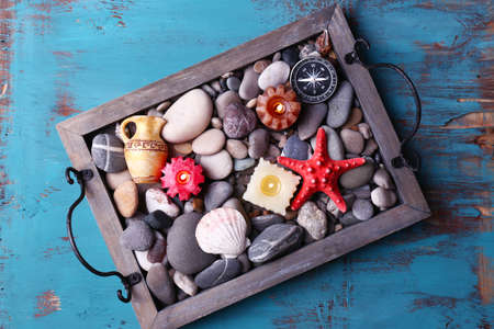 Candles on vintage tray with sea pebbles,starfish and sea shells on wooden  photo