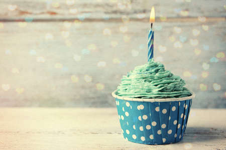 Delicious birthday cupcake on wooden table Stock Photo