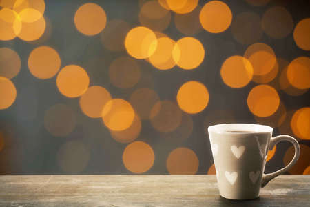 Cup of hot drink on bright background photo