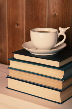 Old books and cup of coffee on table photo
