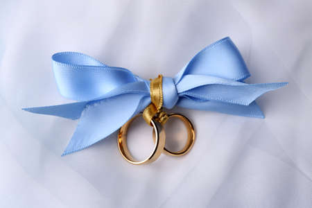 gold ring: Wedding rings tied with ribbon on light background Stock Photo