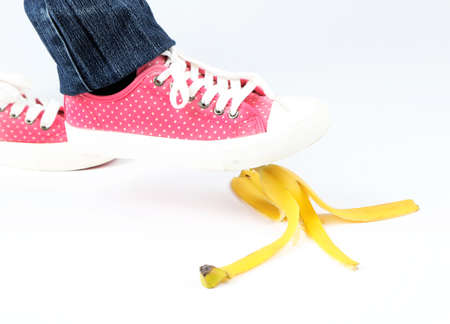 stumbling: Shoe to slip on banana peel and have an accident, isolated on white