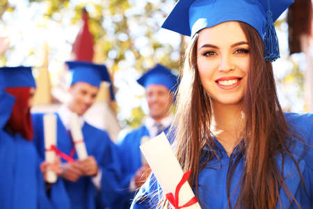 graduacion: Los estudiantes de posgrado con sombrero de graduaci�n y vestido, al aire libre Foto de archivo