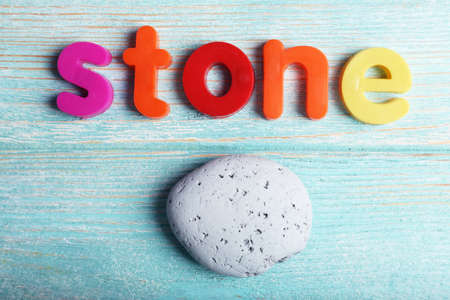 streight: Stone word formed with colorful letters on wooden background Stock Photo