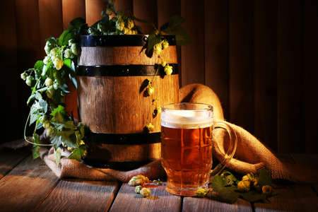 Beer barrel with beer glass on table on wooden background photo