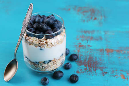 light breakfast: Healthy breakfast - yogurt with  blueberries and muesli served in glass jar, on color wooden background Stock Photo