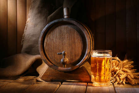 木製の背景にテーブルの上のビールのグラスとビール樽