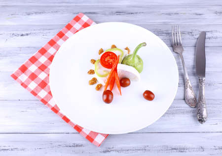 Cottage cheese with vegetables, knife and fork on red checkered napkin on wooden background photo