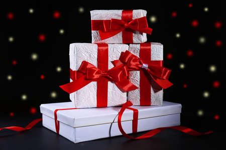 ruban noir: Beaux cadeaux avec des rubans rouges, sur fond sombre