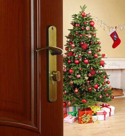 abrir puerta: Abra la puerta con el �rbol de Navidad decorado en la habitaci�n Foto de archivo