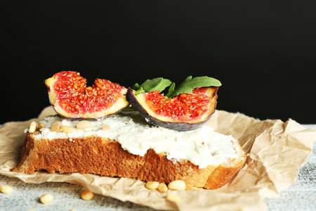 Tasty sandwich with sweet figs and cottage cheese on wooden table, on dark background photo