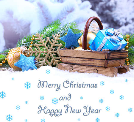 Composition with Christmas decorations in basket on winter background as greeting card photo
