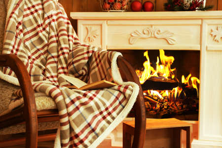Rocking chair with plaid near fireplace Imagens
