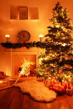 Christmas tree near fireplace in room photo