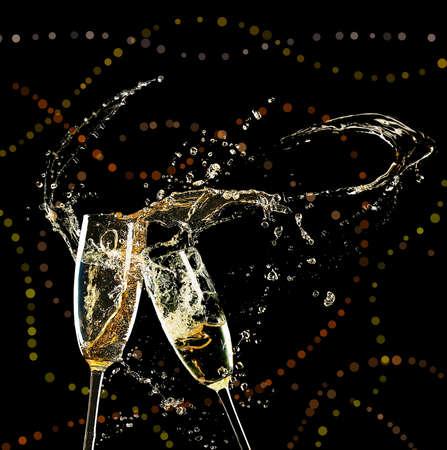 Glasses of champagne with splash, on black