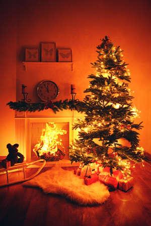 Christmas tree near fireplace in room photo