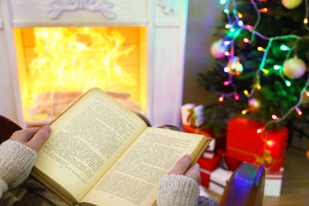 Woman holding book in front of fireplace photo