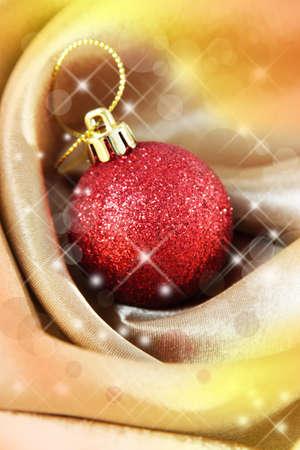 Beautiful Christmas ball on satin cloth, close-up photo