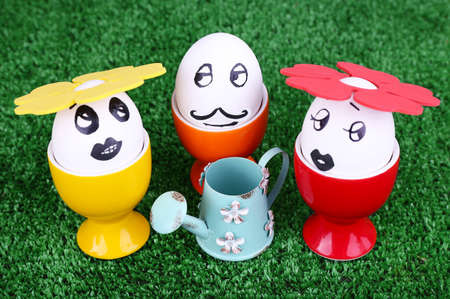 Eggs in egg cups with watering can on green background photo