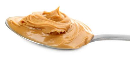 mantequilla: Mantequilla de man� cremosa en la cuchara, aislado en blanco