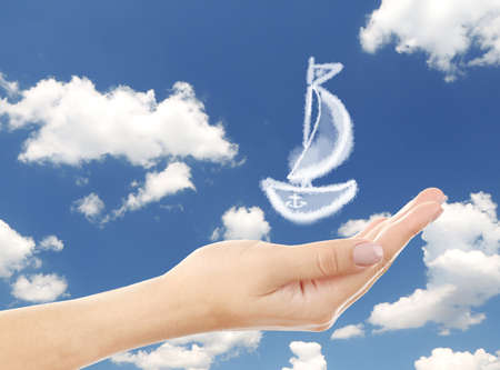 Sailboat clouds shape floating on hand photo