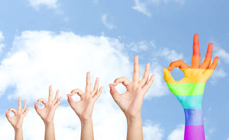 Mans hands on sky background, one hand painted as rainbow flag photo