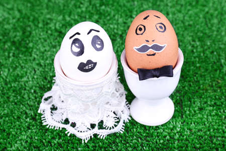 Bride and bridegroom eggs in egg cups on green background photo