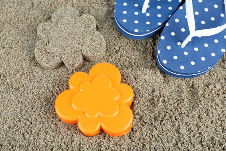 Plastic flower-shaped mold and flip flops on  sand, close-up photo