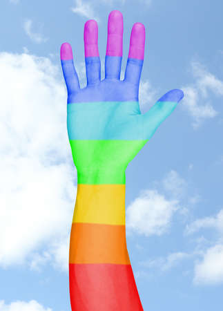 Mans hand painted as the rainbow flag on sky background photo